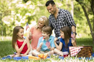 Family enjoys July 4th picnic in summer season. American flags