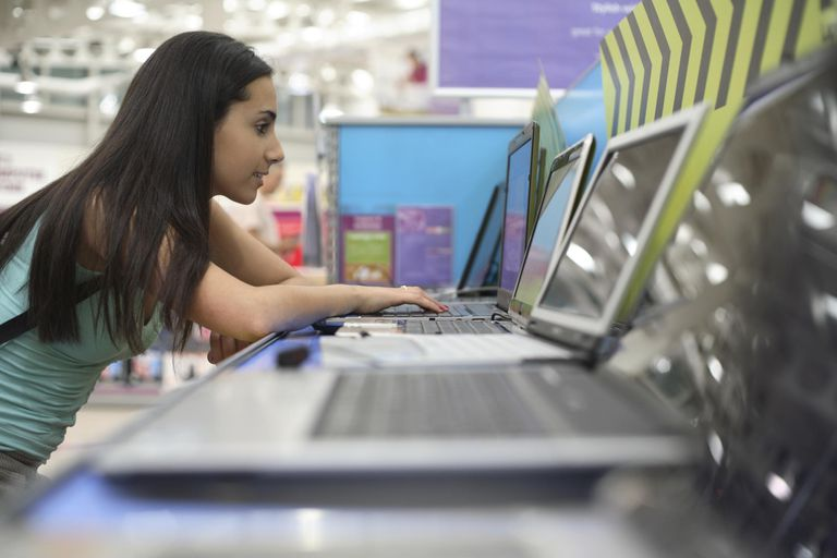 Teenage girl 916-17) using laptop in computer store
