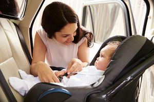 A mother buckling her baby into a carseat