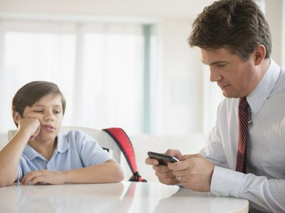 father ignoring son while using cell phone