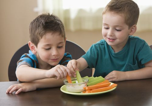 boys eating vegetables with dip