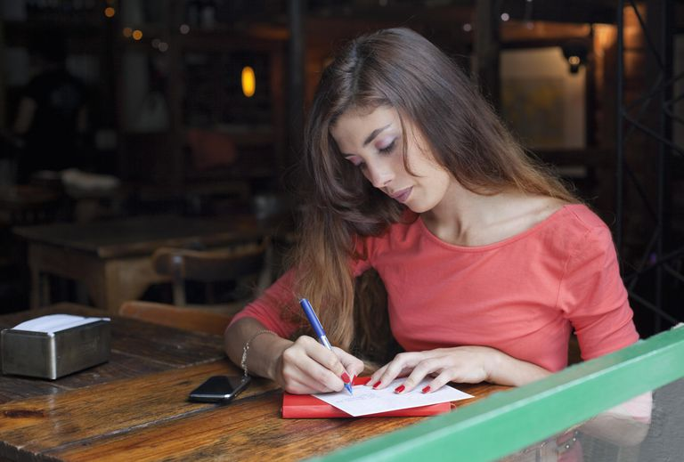 Young woman writing postcards at a café