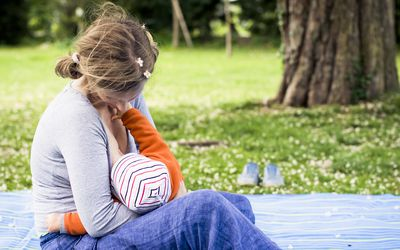Woman breast feeding at the park