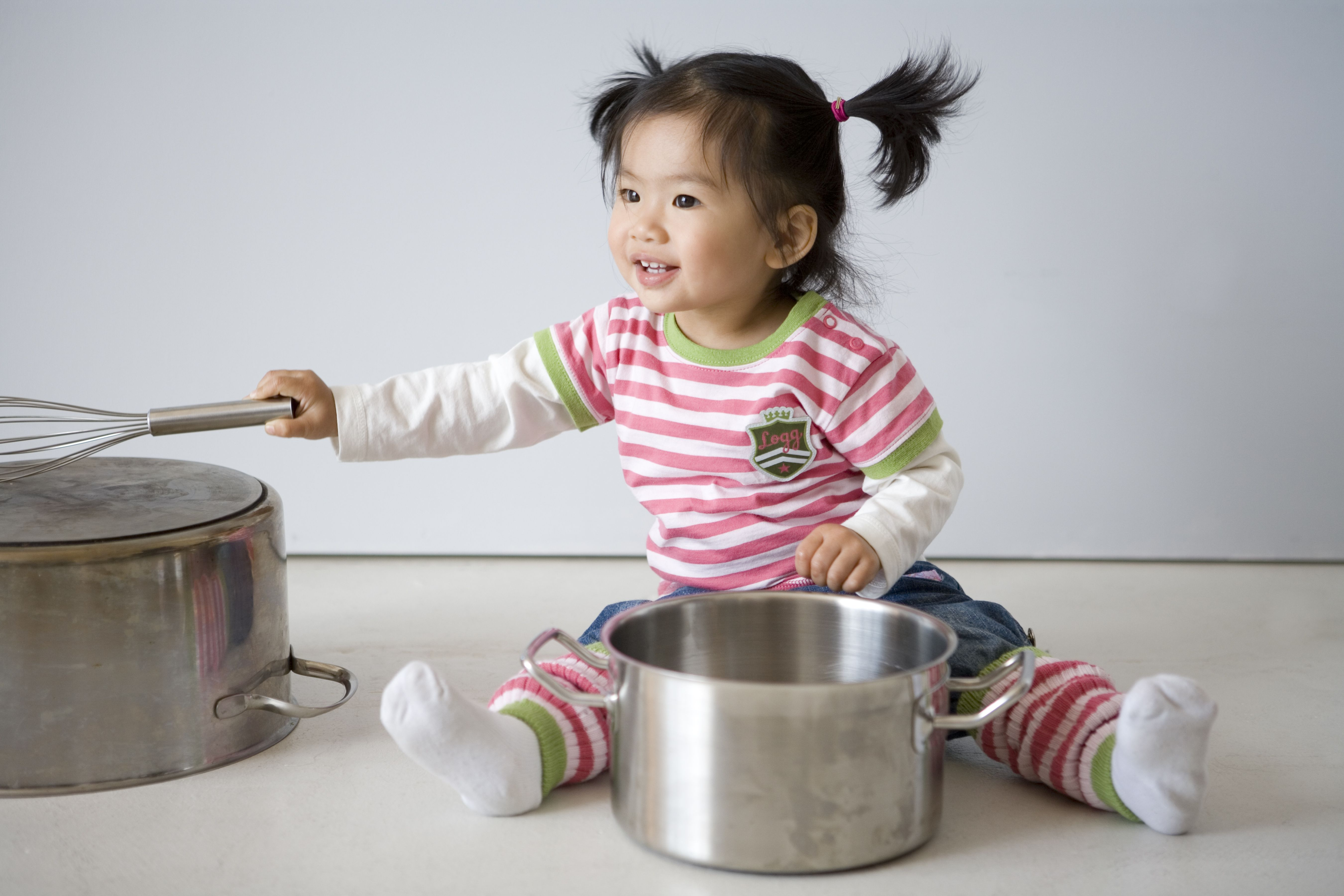 Toddler girl sitting on the floor happily playing with saucepans