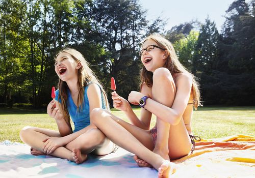 Girls laughing with ice pops in hand