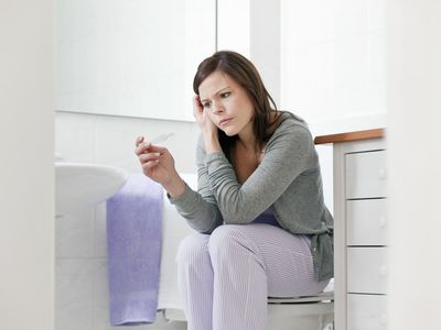 Concerned woman taking pregnancy test