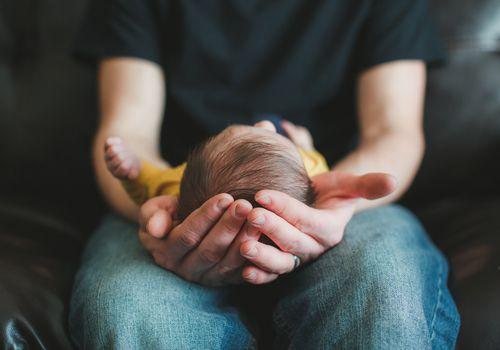 Man cradles baby in hands.