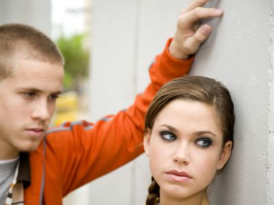 teen girl leaning on wall and looking away from boyfriend