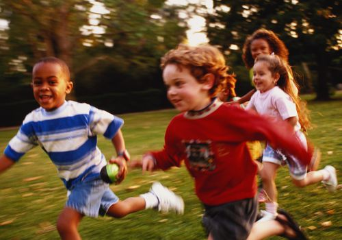 Four young children running outside in a grassy area