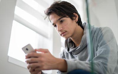 Heartbroken teenage boy sadly looking at smartphone