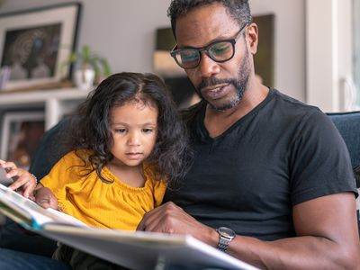 Father reading book with daughter during