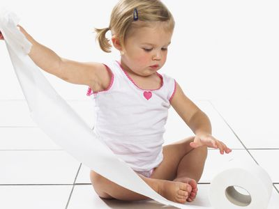 A toddler playing with toilet paper.