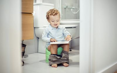 a child sitting on a potty training toilet