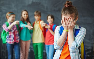 girl covering her face with bullies in background