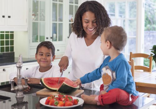 A BIPOC mom cutting up watermelon for her sons