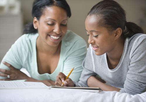 Mother helping tween daughter with homework
