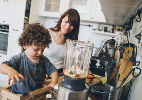 Mom with her toddler boy prepares healthy food