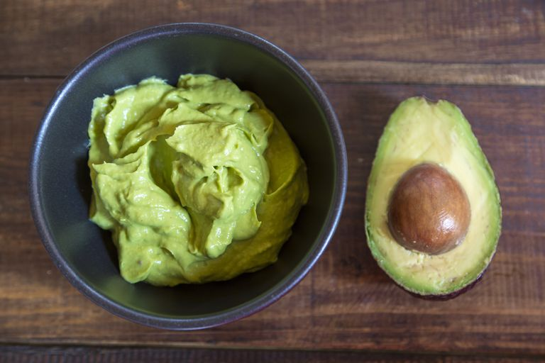 Bowl of guacamole and half of an avocado on wood