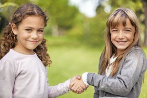 Two girls shaking hands