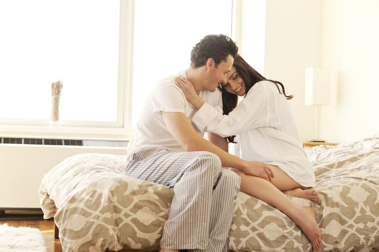 Man and woman on bed hugging. Sex and Breastfeeding for partners of nursing mothers.