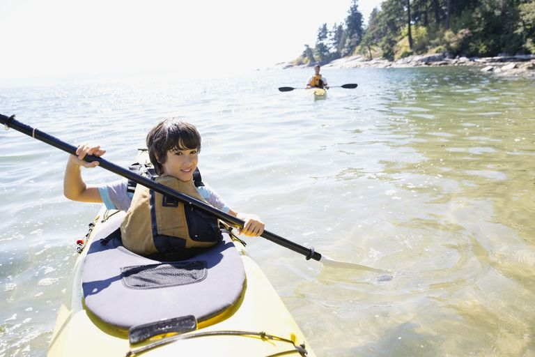 Portrait of boy kayaking in ocean