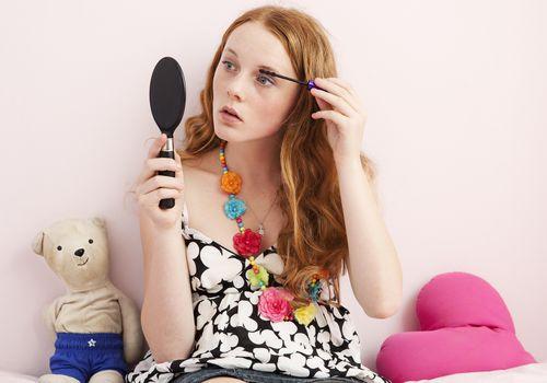 Teenage girl applying mascara