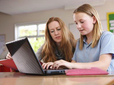 Teacher helping child with ICT skills