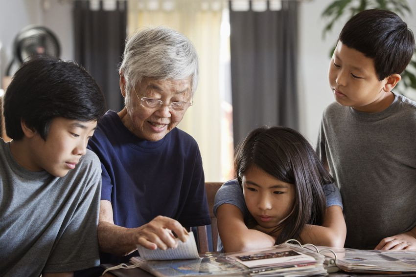 Asian grandmother and grandchildren looking at photo album