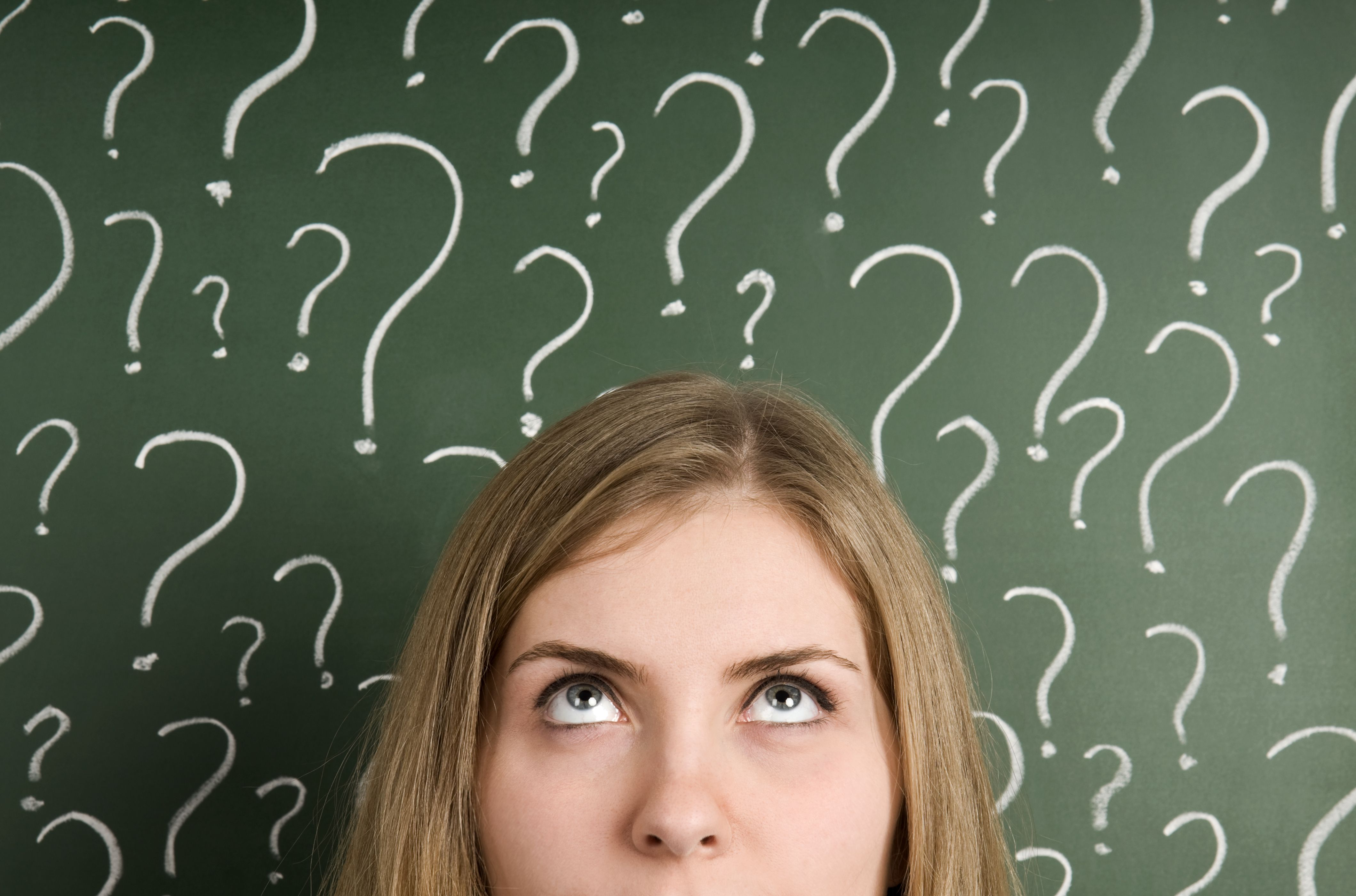 woman looking up at question marks on chalkboard