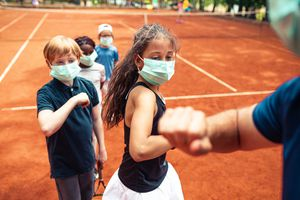 kids on a tennis court wearing masks
