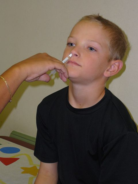 A child gets the FluMist flu vaccine to help decrease his risk of getting the flu.