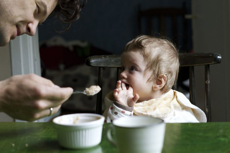 Dad feeding baby cereal