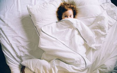 Boy in bed under covers