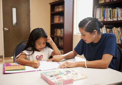 Hispanic woman helping girl with homework in library