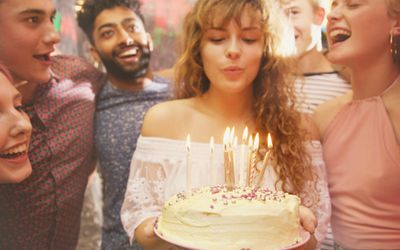 Woman blowing candles while celebrating birthday with friends