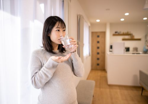 Pregnant woman taking medicine in living room