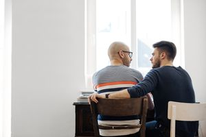 Back shot of a gay couple talking and sitting on desk in their living room.