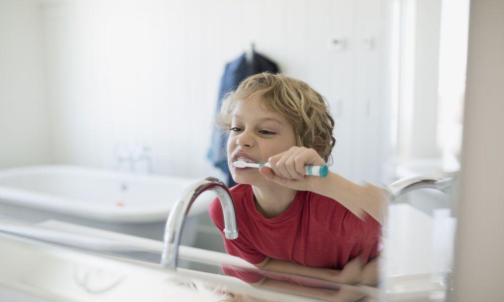 Boy brushing teeth at bathroom mirror