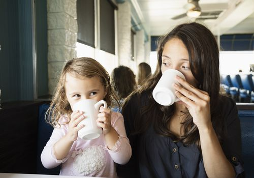 Mom and toddler drinking coffee out of white mugs