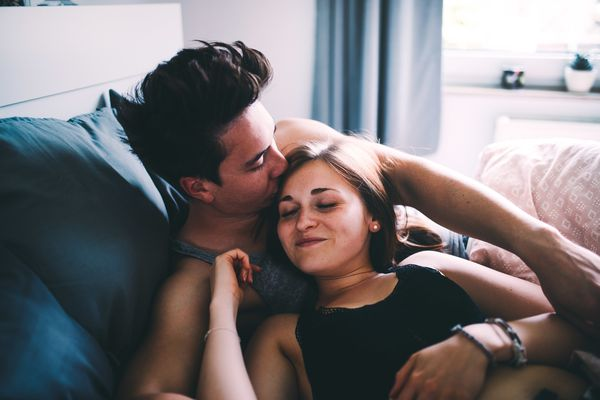 Couple in bed, man is kissing woman's head