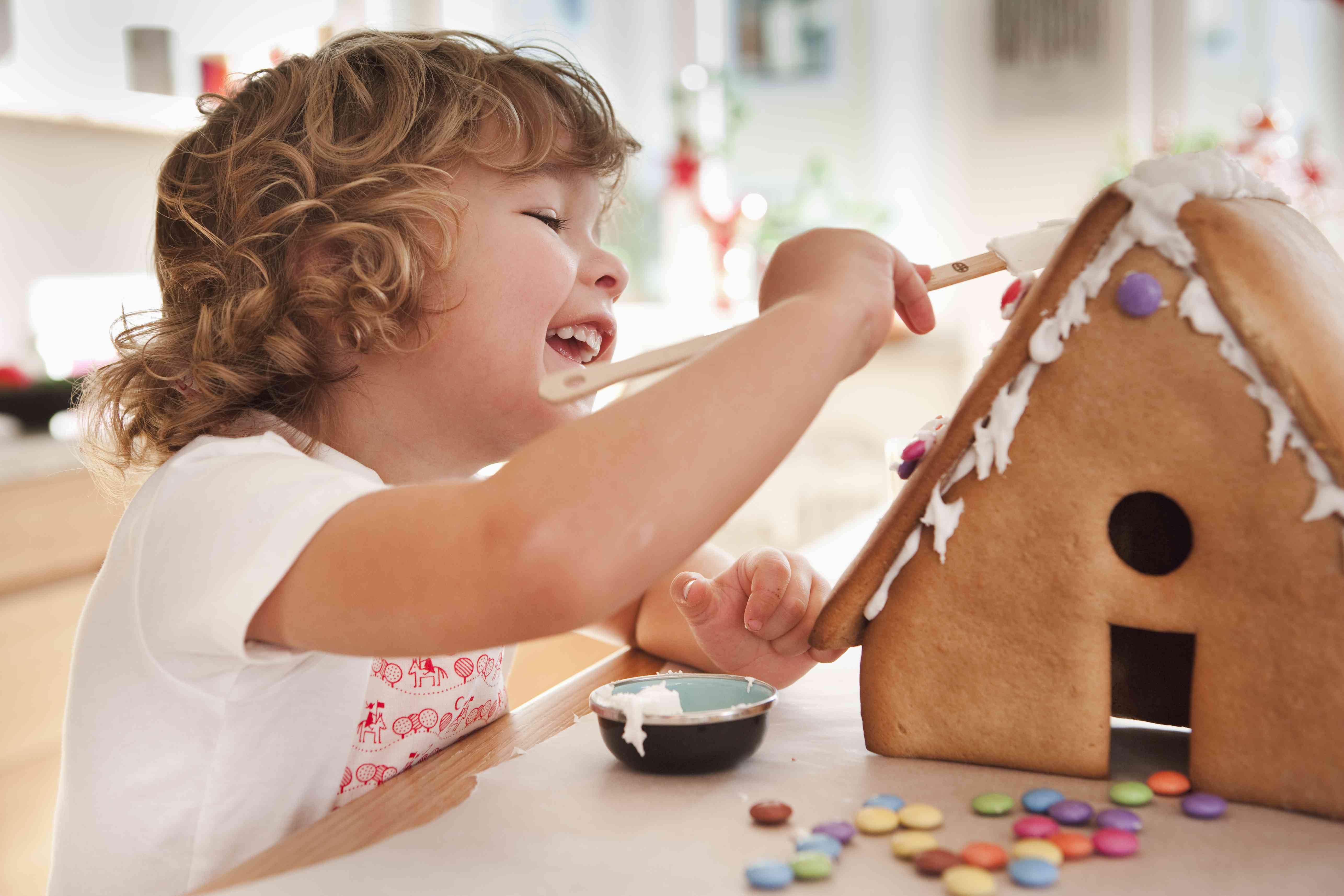 Young child decorating a gingerbread house