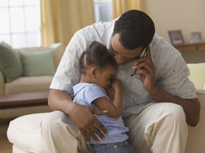 Father on the phone hugging child