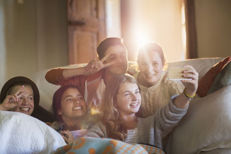 Group of smiling teenagers taking selfie on sofa in living room