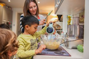 Woman helping kids with a mixer in the kitchen