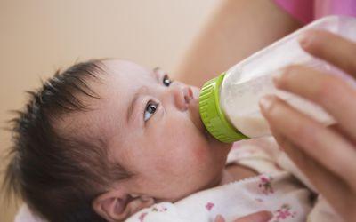 Mother bottle feeding their baby