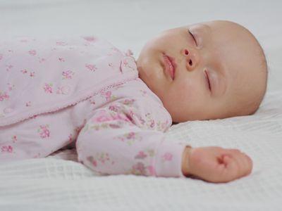 baby girl sleeping on her back on white bedding