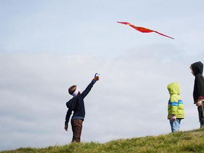 3 kids flying a kite outside
