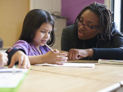Paraprofessional helping a child in a classroom.