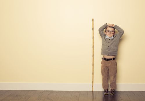 Boy stands next to ruler on wall to measure height