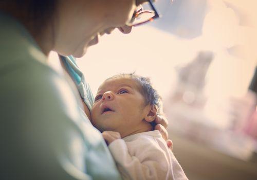 Mom smiling at newborn at hospital